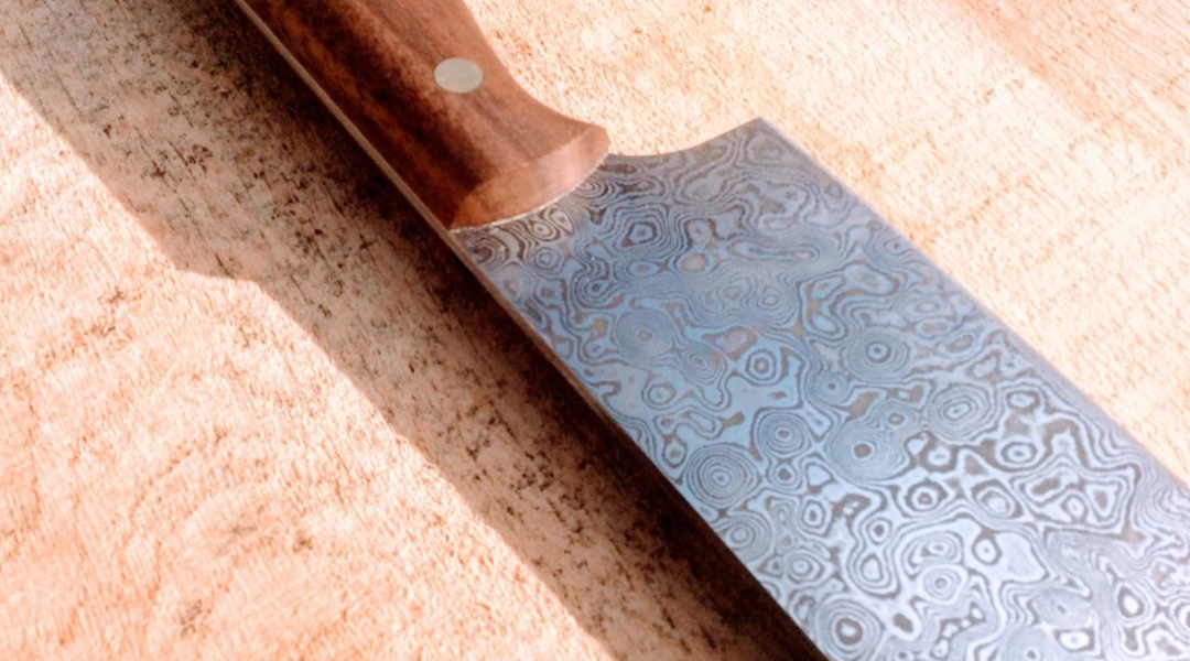 closeup of knife blade showing intricate swirling patterns in the metal