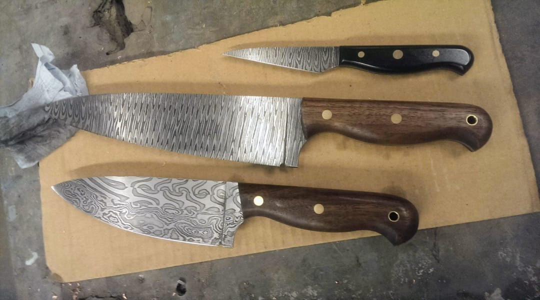 3 damascus steel chef knives of different sizes each with a unique swirling pattern in the blade