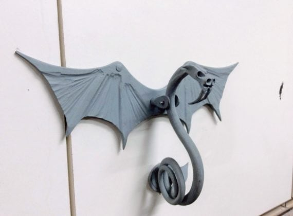 Steel door knocker in the shape of a slender dragon with wings outstretched